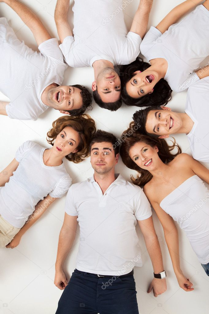 Friends posing laying down on the floor looking at camera — Stock Photo #5939817