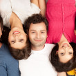 Group of friends laying on the floor, smiling — Stock Photo #6078660