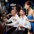 Friends playing the slots — Stock Photo