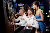 Friends playing the slots — Stok fotoğraf