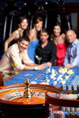 Friends watching the spinning roulette — Stock Photo