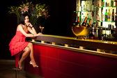 Dama de vermelho sentado no bar — Fotografia Stock