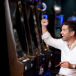 Handsome man winning at the slot machine — Foto de Stock