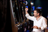 Handsome man winning at the slot machine — Stock Photo