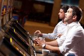 Handsome men playing the slot machine — Stock Photo