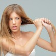 Young woman pulling her damadged hair — Stock Photo
