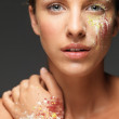Beautiful woman loose colored powders on face — Stock Photo #6277193