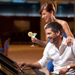 Elegant couple playing the slot machine - Stock Photo