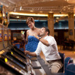 Man and woman playing he slot machine - Stock Photo
