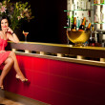 Woman red dress at bar counter smiling — Stock Photo