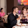 Happy couple at restaurant table toasting - Stock Photo