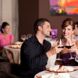 Foto Stock: Happy couple at restaurant table toasting