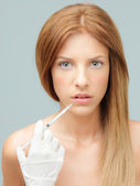 Young woman injecting colagen in lips — Stok fotoğraf
