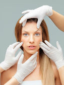 Beautiful face being examinated plastic surgeons hands — Stock Photo