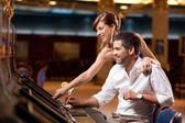 Couple playing the slot machine — Stock Photo