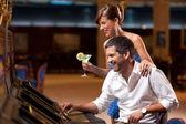 Elegant couple playing the slot machine — Stock Photo