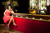 Woman red dress at bar counter smiling — Stock Photo