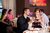 Coppia felice al ristorante tavolo tostatura — Foto Stock