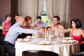 Young toasting restaurant table — Stock Photo