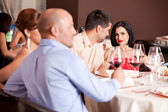 Happy couple at restaurant table talking — Stock Photo