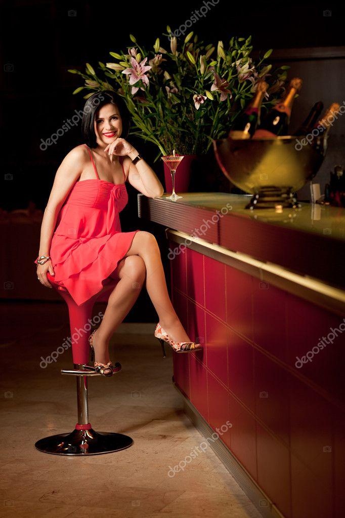 Woman red dress at bar counter smiling stock photo 169 shotsstudio
