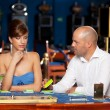 Flirting couple playing cards in a casino — Stok fotoğraf