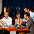 Stock Photo: Laughing friends playing cards in a casino
