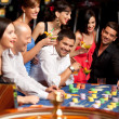 Happy caucasian friends playing roulette in casino — Stock Photo #6653240