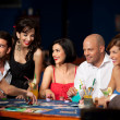 Laughing friends playing cards in a casino — Stock Photo