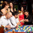 Happy caucasian friends playing roulette in casino — Stock Photo #6653246