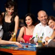 Laughing friends playing cards in a casino - Stock Photo