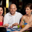 Handsome blackjack player with two elegant women - Stock Photo