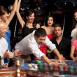 Happy caucasian friends playing roulette in casino — Stock Photo