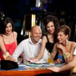 Happy caucasian friends playing blackjack in casino — Stock Photo #6653254