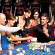 Happy caucasian friends playing roulette in casino — Stock Photo #6653255