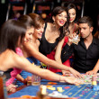 Happy caucasian friends playing roulette in casino — Stock Photo #6653257