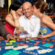 Wealthy blackjack player flirting with two women — Stock Photo