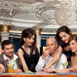Happy caucasian friends playing blackjack in casino — Stock Photo