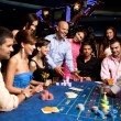 Happy friends playing roulette in a casino — Stock Photo