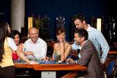 笑在赌场中的朋友玩纸牌 — 图库照片