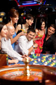 Happy caucasian friends playing roulette in casino — Stok fotoğraf