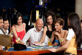 Happy caucasian friends playing blackjack in casino — Stock Photo