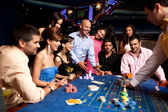 Happy friends playing roulette in a casino — Stok fotoğraf