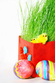 Colored easter eggs and chickens in green grass — Stock Photo