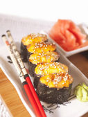 Hot sushi on plate with chopsticks — Stock Photo