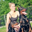 Pretty women with own dobermans — Stock Photo #6234657