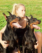 Pretty women with own dobermans — Stock Photo