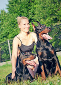 Pretty women with own dobermans — Stockfoto