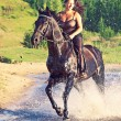 Sexy women galloping  on  horse at lake - Stock Photo