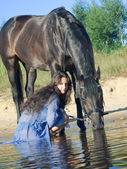 Pretty women with yours horse in lake — Stock Photo